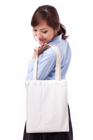 happy, smiling asian woman carrying reusable cotton bag, concept of recycle for better environment