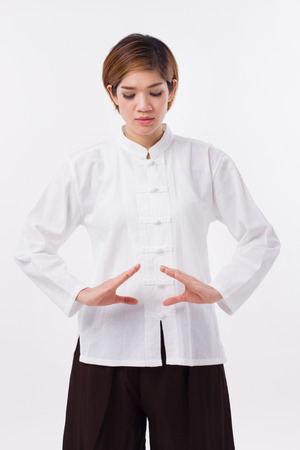 taichi: peaceful, strong, confident asian woman practice kungfu qigong, belly center dantian concentration