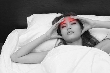 relieve: sick woman on bed massaging her head to relieve pain or stress