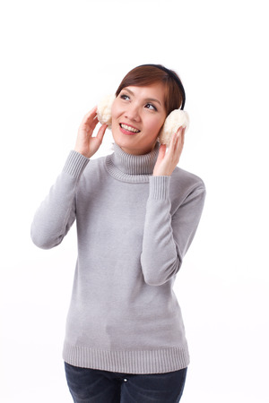 earmuffs: happy, smiling, positive asian woman looking up, in fall or winter dress with earmuffs Stock Photo
