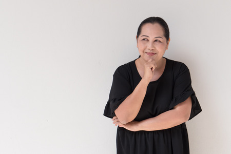 middle aged asian woman thinking, planning with text space