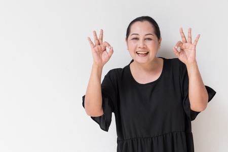 old asian: middle age woman giving ok hand sign, concept of positivity, acceptance, agreement