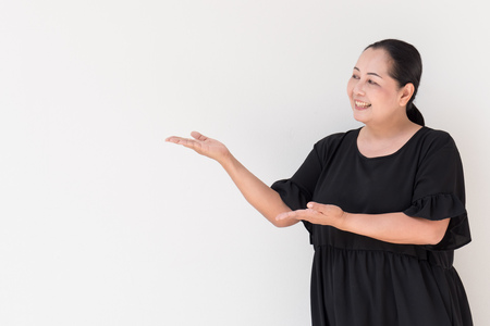 suggesting: middle age woman pointing up, showing, suggesting, presenting something
