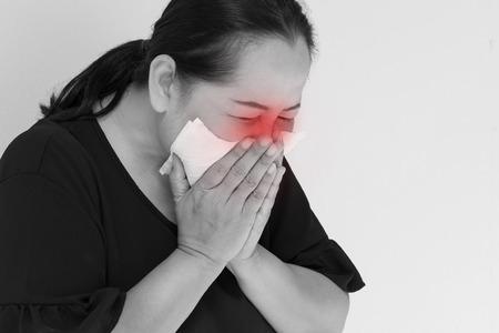 zieke vrouw met verkoudheid of griep die niezen met papieren zakdoekje