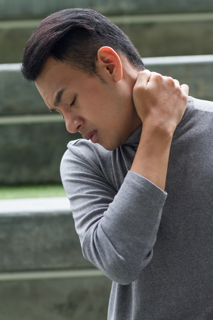 exhausting: asian man suffering from neck pain, arthritis, gout symptoms Stock Photo