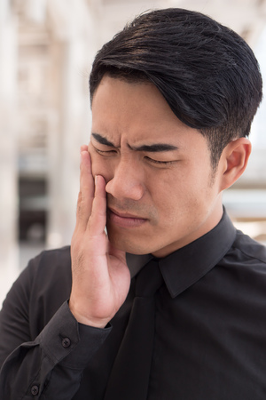 man suffering from toothache, oral problem Stock Photo