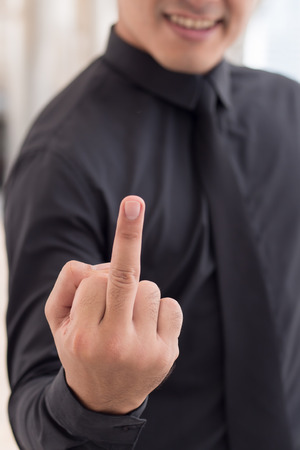 offend: man showing middle finger, rude hand sign Stock Photo