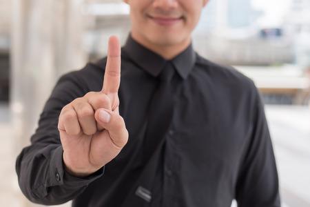 empresario señalando el gesto de la mano número 1 dedo