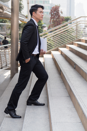 stepping: confident businessman stepping up to success Stock Photo
