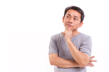 middle aged asian man thinking, studio isolated portrait