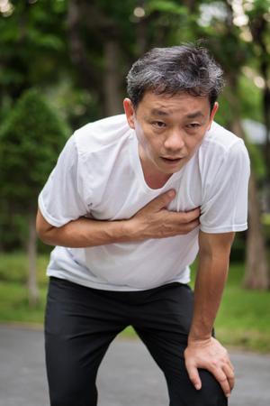 Agotado, jadeando, paro cardiaco ejecutando hombre mayor, parque al aire libre Foto de archivo - 80827619