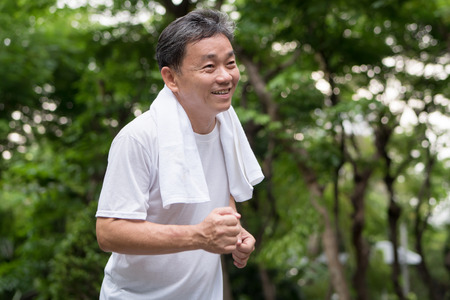 happy smiling old man running in nature park outdoor scene, middle aged to senior age range