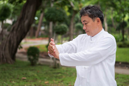 old man practicing kungfu or tai chi in the park, healthy lifestyle meditation exercise concept