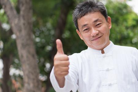 asian kung fu senior man showing thumb up hand gesture