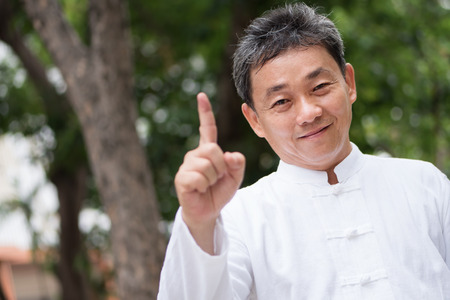 asian kung fu senior man showing number 1 hand gesture