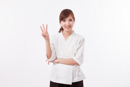 Donna spa terapista che indica 3 dita, contando, numerazione Archivio Fotografico - 81848100
