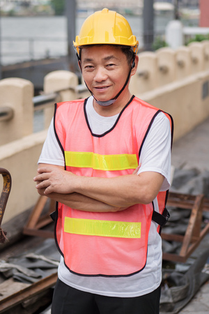 obrero: happy smiling construction worker standing with pile of raw material