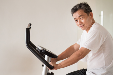 old senior man cycling, exercising, working out in gym with modern cycling machine