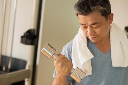 Senior Aziatische man uit te werken, krachttraining met halter Stockfoto - 82417817