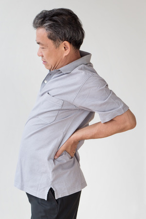 man suffering from back pain, hand holding back Stock Photo
