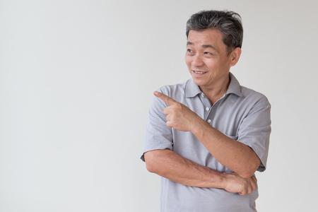 Oud, van middelbare leeftijd, senior Aziatische man op zoek en wijzende vinger weg gebaar Stockfoto - 83220310