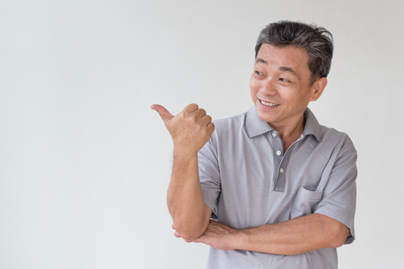 old, middle aged, senior asian man pointing thumb up finger gesture