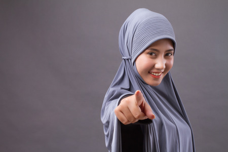 happy smiling confident muslim woman pointing at you, with hijab or head scarf