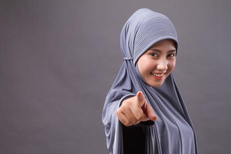 hijab 또는 head 스카프와 함께 당신을 가리키는 행복 웃는 자신감 이슬람 여자
