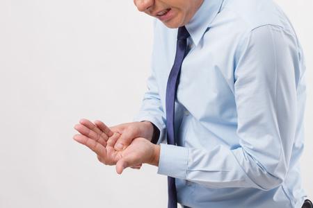Man suffering from trigger finger, arthritis, wrist pain