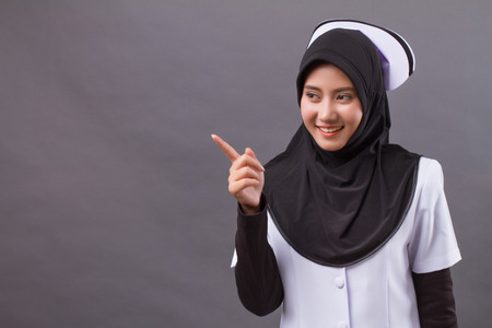 Muslim nurse pointing up finger Stock Photo