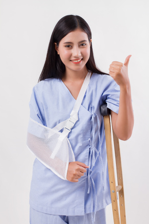 injured woman patient pointing thumb up gesture away Stock Photo