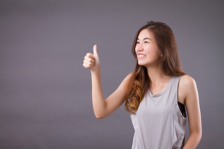 exited woman giving thumb up studio isolated portrait