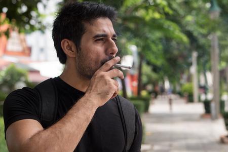 Rauchende Zigarette des asiatischen Mannrauchers Standard-Bild