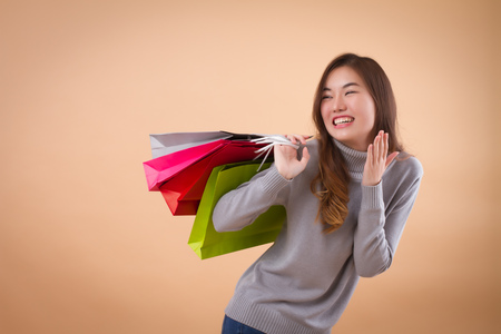 happy, excited woman shopper or customer with shopping bag