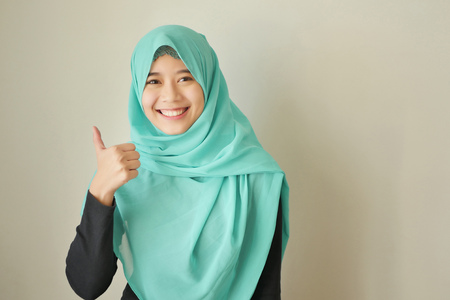 muslim woman with hijab pointing thumb up