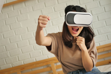 woman with fighting game VR headsets Stock Photo