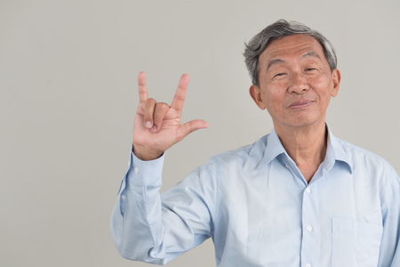 happy, positive senior old man showing I love you hand gesture