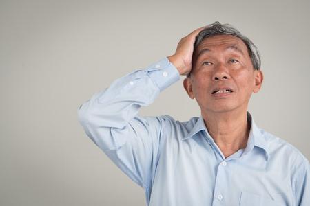 sick stressed old senior man headache, dizzyness, sinus inflammation, stress, migraine, alzheimer, parkinson disease concept Foto de archivo