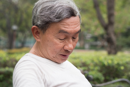 sad hopeless frustrated old retired senior man sitting in public park, urban poverty concept