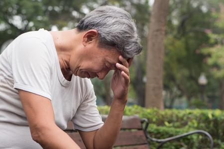homem sênior aposentado frustrante impossível triste sentado no parque público, conceito de pobreza urbana Foto de archivo
