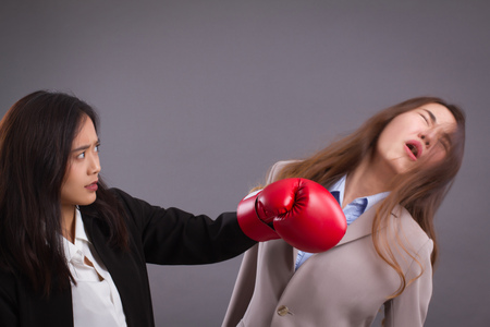 Southpaw business woman beating surprised impact sucker punch to competitor
