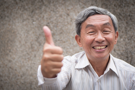 senior man giving thumb up gesture