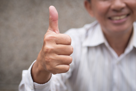 senior man giving thumb up gesture