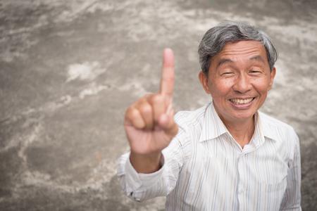 happy old senior man pointing up 1 finger