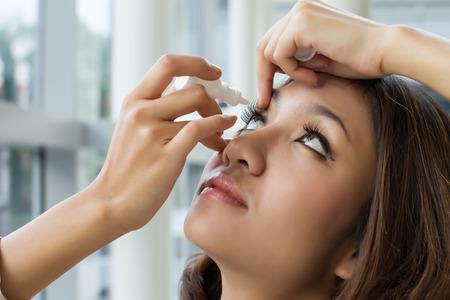 woman using eye drop, eye lubricant to treat dry eye or allergy Stock Photo