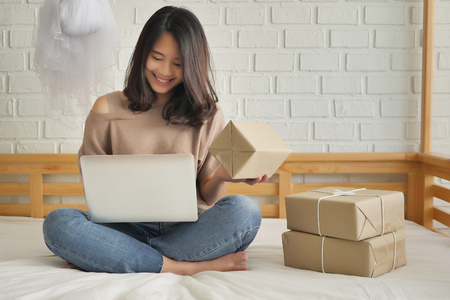 happy woman with computer and product parcel box at home, work at home merchandise delivery concept