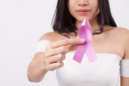 Woman hand holding violet ribbon bow, testicular cancer awareness symbol; violet ribbon for medical, charity fund raising concept for testicular cancer patient or testicle tumor prevention Stock Photo