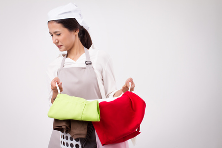 Unhappy Asian woman carrying stinking heavy laundry basket