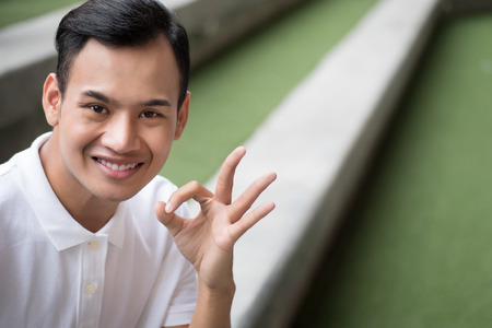 ok man; happy man giving ok gesture; smiling friendly man showing approval okay hand, agreed ok hand sign; happy smiling man shows accepting ok finger gesture concept of agreement, yes, good job Stock Photo