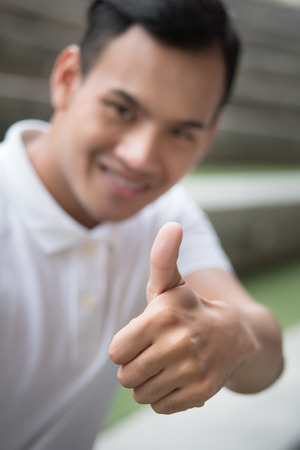 happy man giving thumb up gesture; smiling friendly man showing approval, agreed thumb up; happy smiling man shows thumb up hand sign concept of agreement, ok, yes, good; young adult asian man model Stock Photo